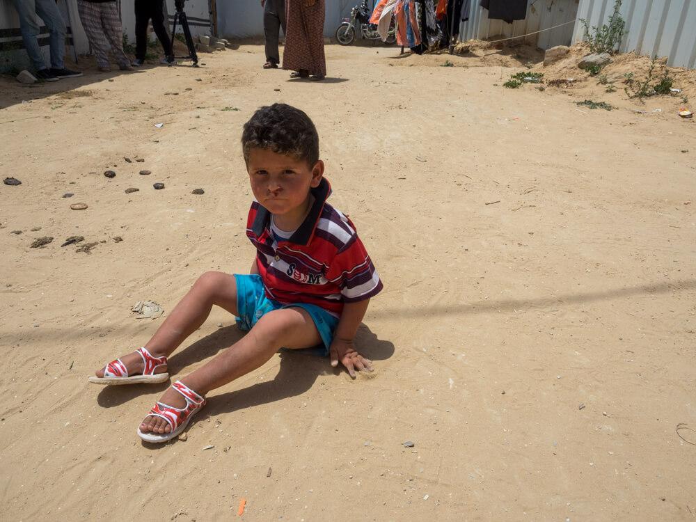 Lacking a wheelchair, Ahmad Najjar scoots on the ground around the caravan. (Photo: Dan Cohen)