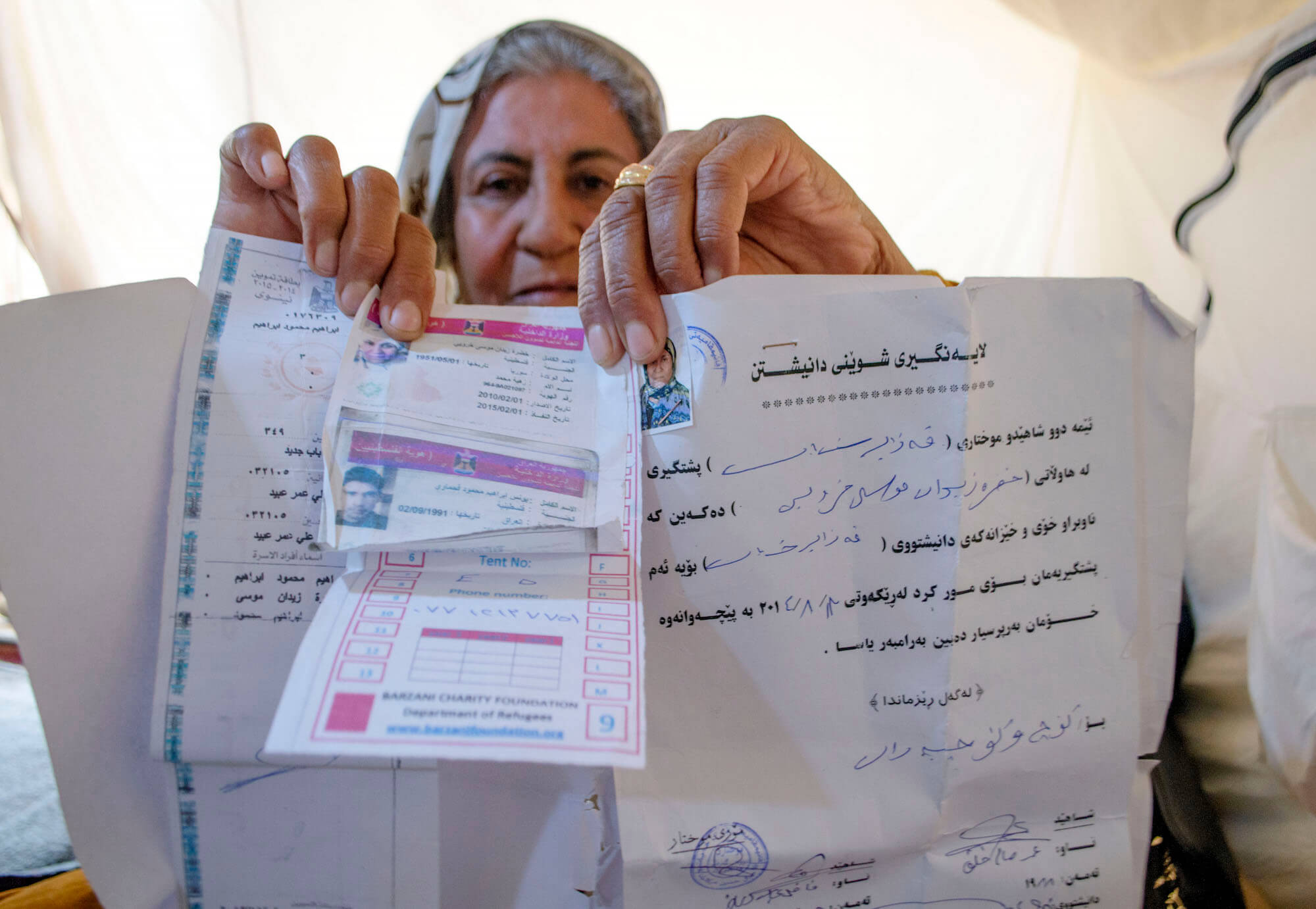 "Khadra Ibrahim holds up her refugee documents. Ibrahim was born in Khan al-Sheikh refugee camp in Syria several years after the Nakba. Baharka is her fourth refugee camp. ""All the Palestinian here are tired,"" she says. (Photo: Abed Al Qaisi)"