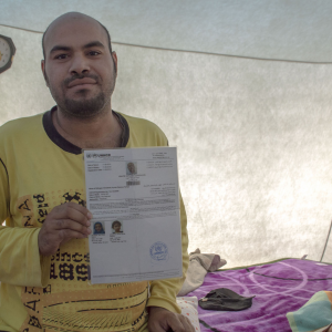 "Ayhab Aldadeedi's family fled Haifa in 1948. Aldadeedi, born in Iraq, holds the documents showing his Palestinian refugee status. ""Nakba, which Nakba? My whole life has been a string of catastrophes,"" he says. (Photo: Abed Al Qaisi)"