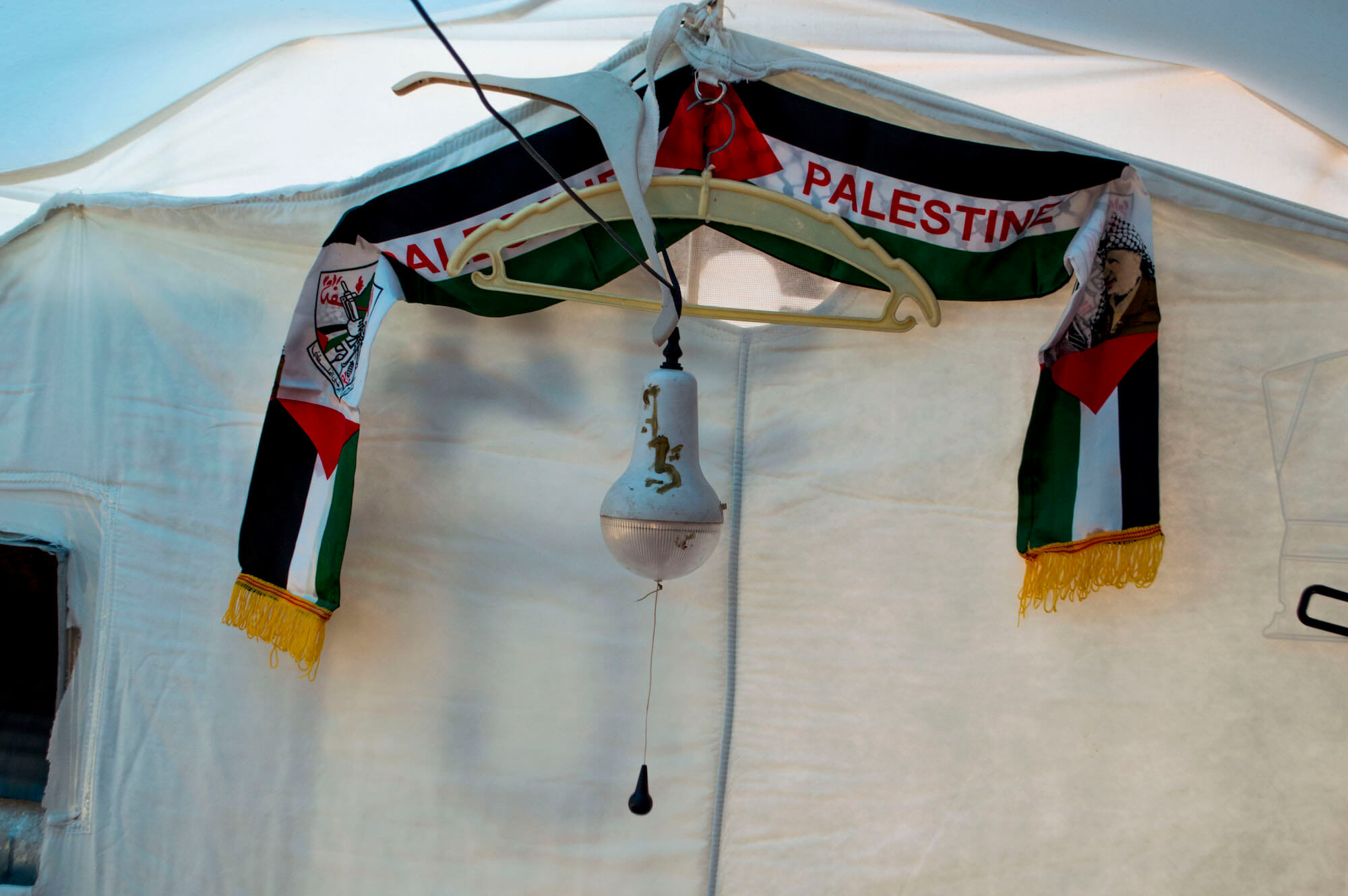 A small Palestine scarf adorns the plastic wall of one of the tents at Baharka Camp. Talk of Palestine is frequent, and on Nakba day many of the Palestinian refugees at Baharka will reflect back on the similarities between their current hardship and the hardship of their parents and grandparents when they first fled violence in 1948. (Photo: Abed Al Qaisi)