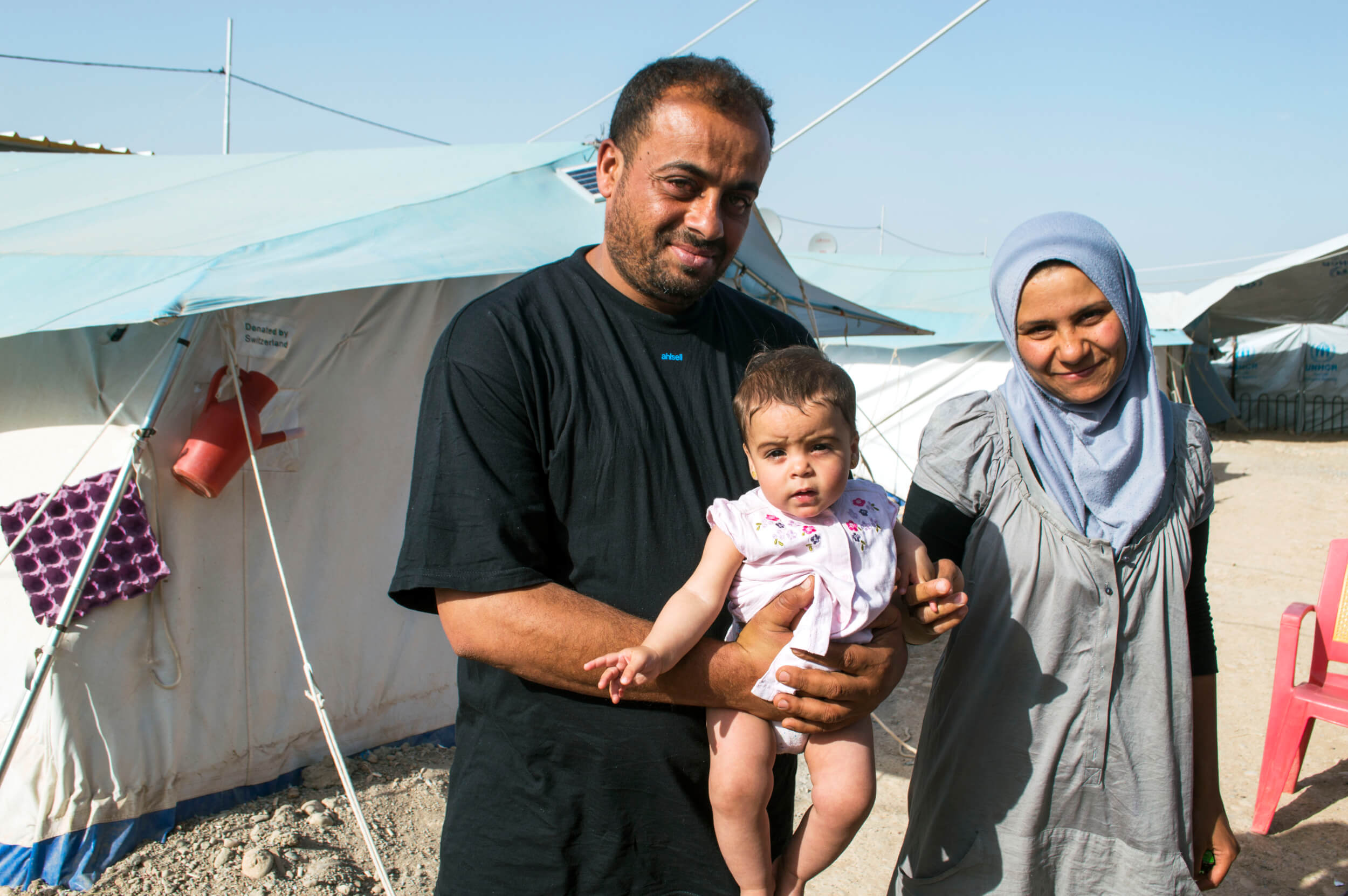 The Awad family stands outside, Haya the newest member is only six months old. Haya was born at Baharka. (Photo: Abed Al Qaisi)