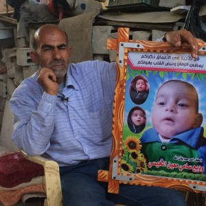 Moaeen Al-Kheysi sits in his home holding a poster commemorating the life of his grandson Wadie. (Photo: Dan Cohen)