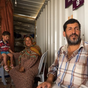Ahmad Najjar and his parents sit in the donated shipping container they have lived in since last fall. (Photo: Dan Cohen)