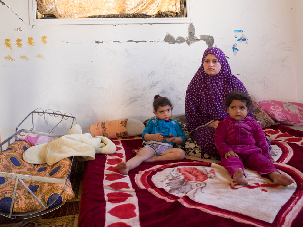 Rania Al-Kheysi sits with her two daughters Sona and Janat next to the crib of the brother Wadie who froze to death this winter. (Photo: Dan Cohen)