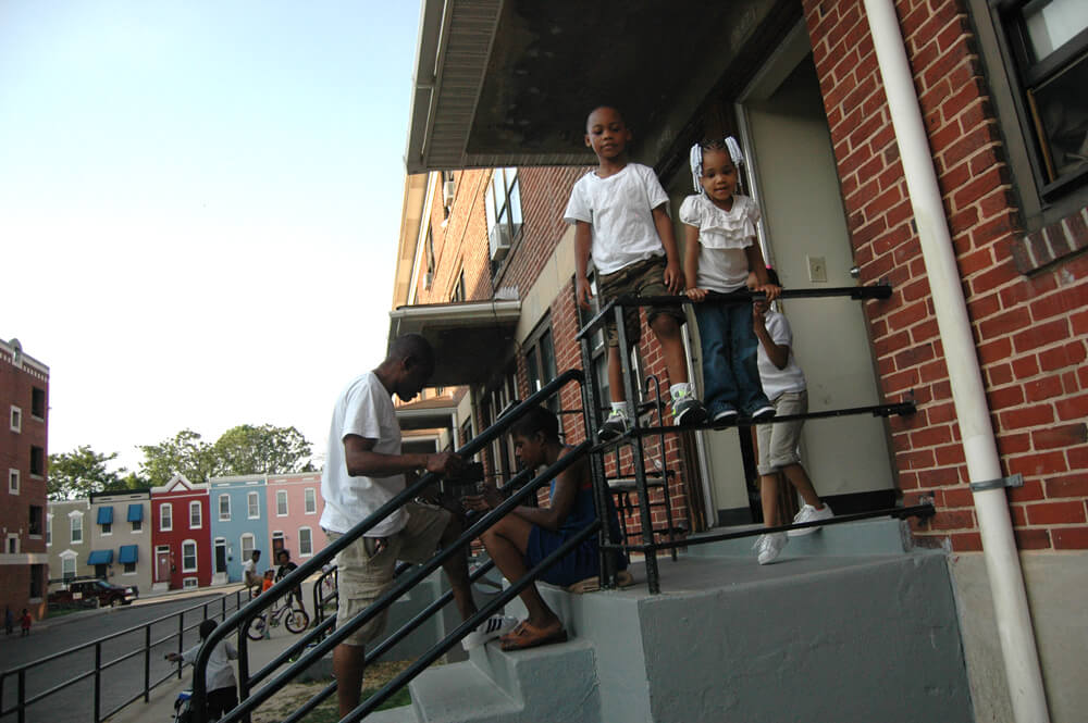 Gilmor Homes residents on their front stoop, Baltimore. (Photo: Allison Deger)