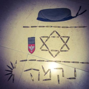 "Image posted on Facebook in July, 2014 showing ""Revenge"" written in M16/M4 bullets next to the shoulder tags of the the Kfir Brigade and a general IDF beret. (Image: muddleast.wordpress.com)"