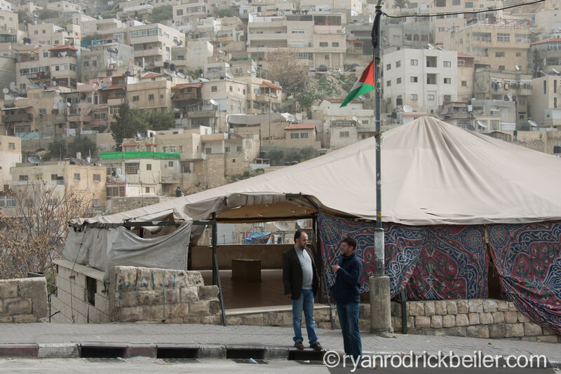 Daoud Al-Ghoul talks with a neighbor next to a protest tent built by local activists in the East Jerusalem neighborhood of Silwan, March 3, 2014. (Photo: Ryan Rodrick Beiler)