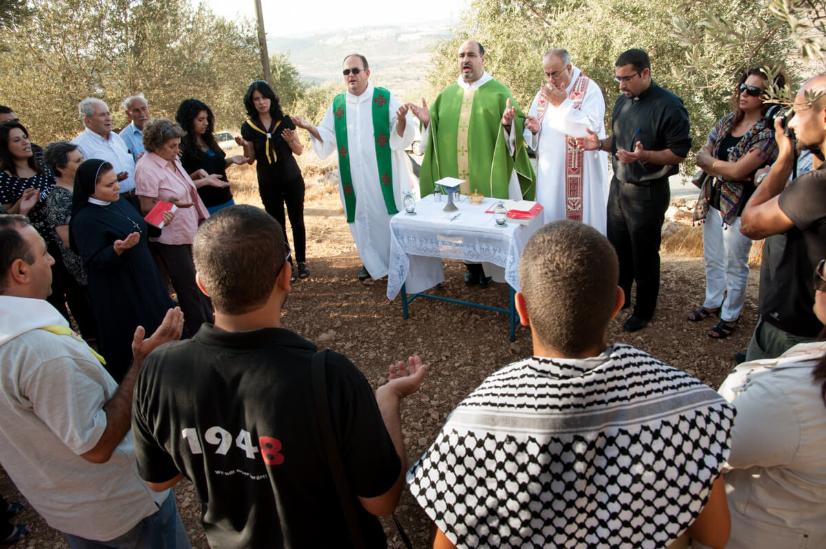 Palestinians hold a Catholic mass as a weekly nonviolent witness against the Israeli separation wall in the West Bank village of Beit Jala, September 7, 2012. (Photo: Ryan Rodrick Beiler)