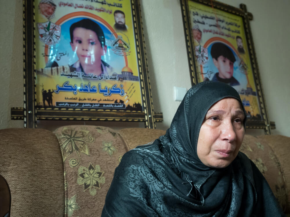 Sharifa Bakr sits in front of posters commemorating Ahed and Zachariah Bakr, photo by Dan Cohen