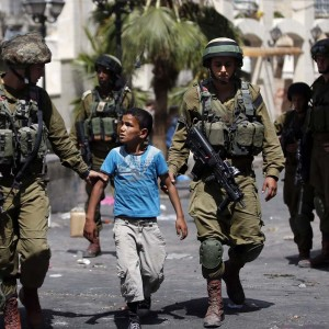 Israeli soldiers arrest a young Palestinian boy following clashes in the center of the occupied West Bank town of Hebron, June 20, 2014. (Photo: Thomas Coex/AFP)