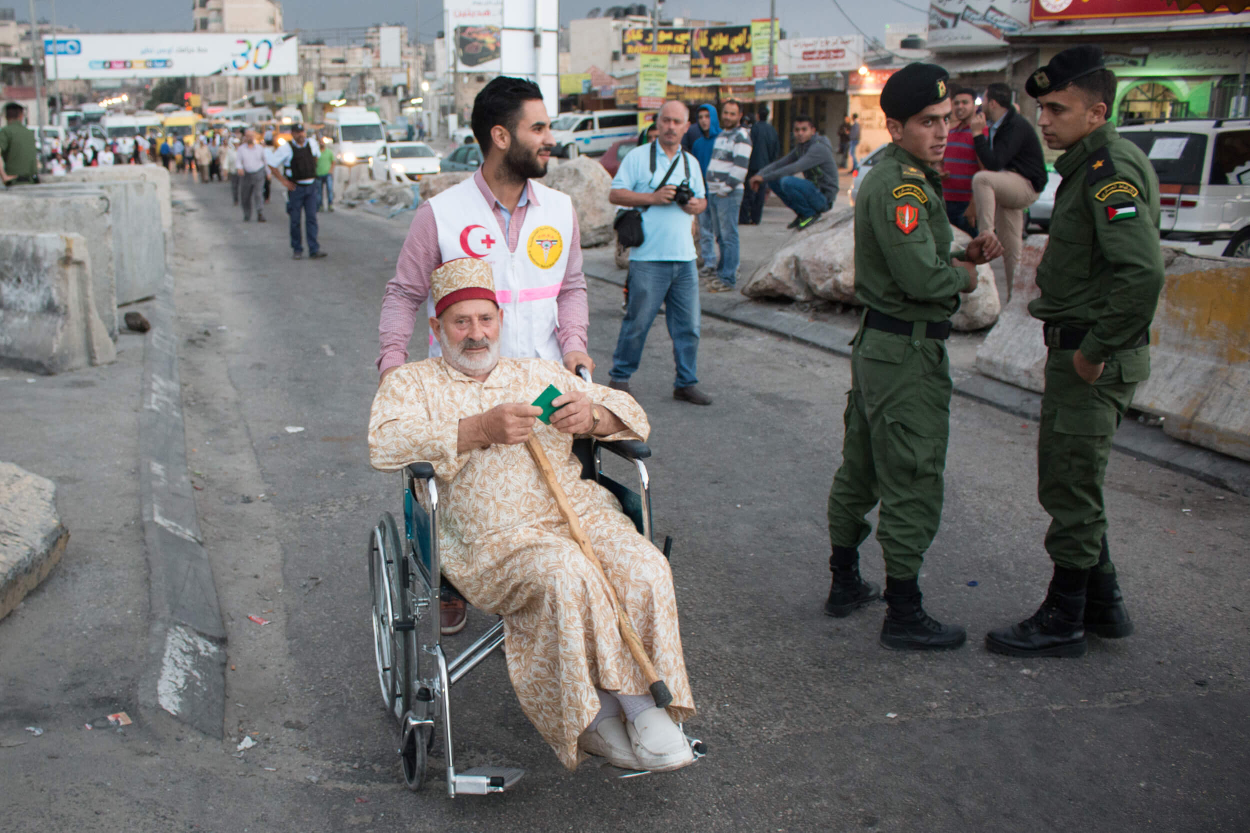 A PMRS (Palestine Medical Relief Society) volunteer helps a man from Nablus on his way into Qalandia checkpoint beside Palestinian District Coordination soldiers.  PMRS and the Palestinian Red Crescent Society maintain a volunteer presence every Friday during Ramadan at Qalandia checkpoint.  The Palestinian soldiers coordinate with the Israeli military to facilitate the crossing on Fridays during Ramadan. (Photo: Karam Saleem)