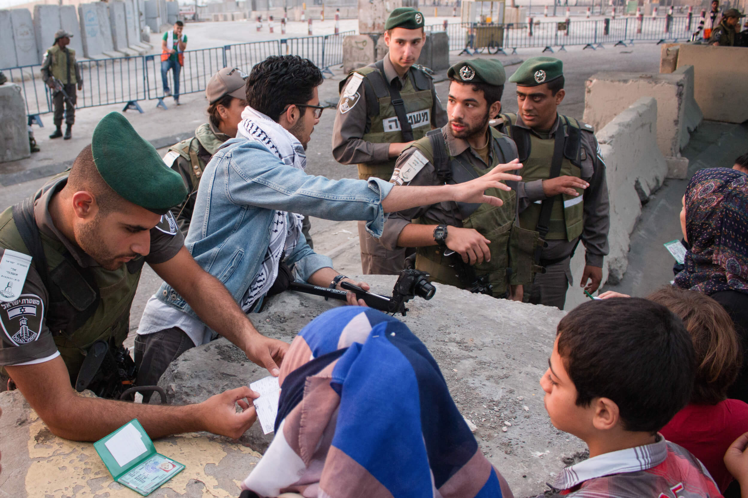 An ISM (International Solidarity Movement) activist confronts an Israeli soldier checking the age of a boy in line. Palestinian children from the West Bank under 12-years-old are allowed entry into Jerusalem for Friday prayers.  Soldiers routinely check the ID cards of young boys to make sure they meet age requirements.(Photo: Karam Saleem)