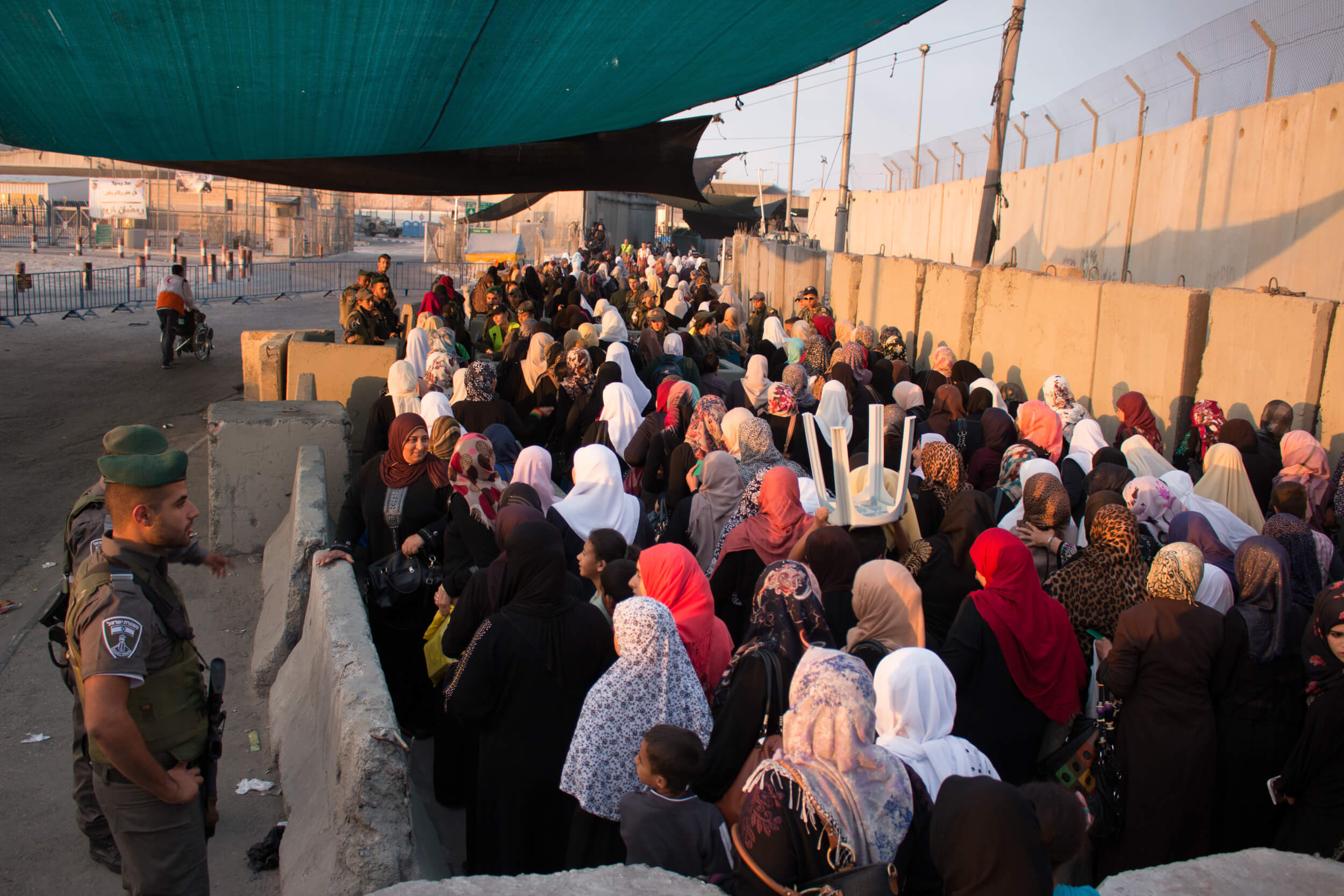Women queue at Qalandia checkpoint around 5am, on their way into Jerusalem for Friday prayers at Al Aqsa Mosque. Qalandia checkpoint is segregated for men and women on Fridays during Ramadan. (Photo: Karam Saleem)