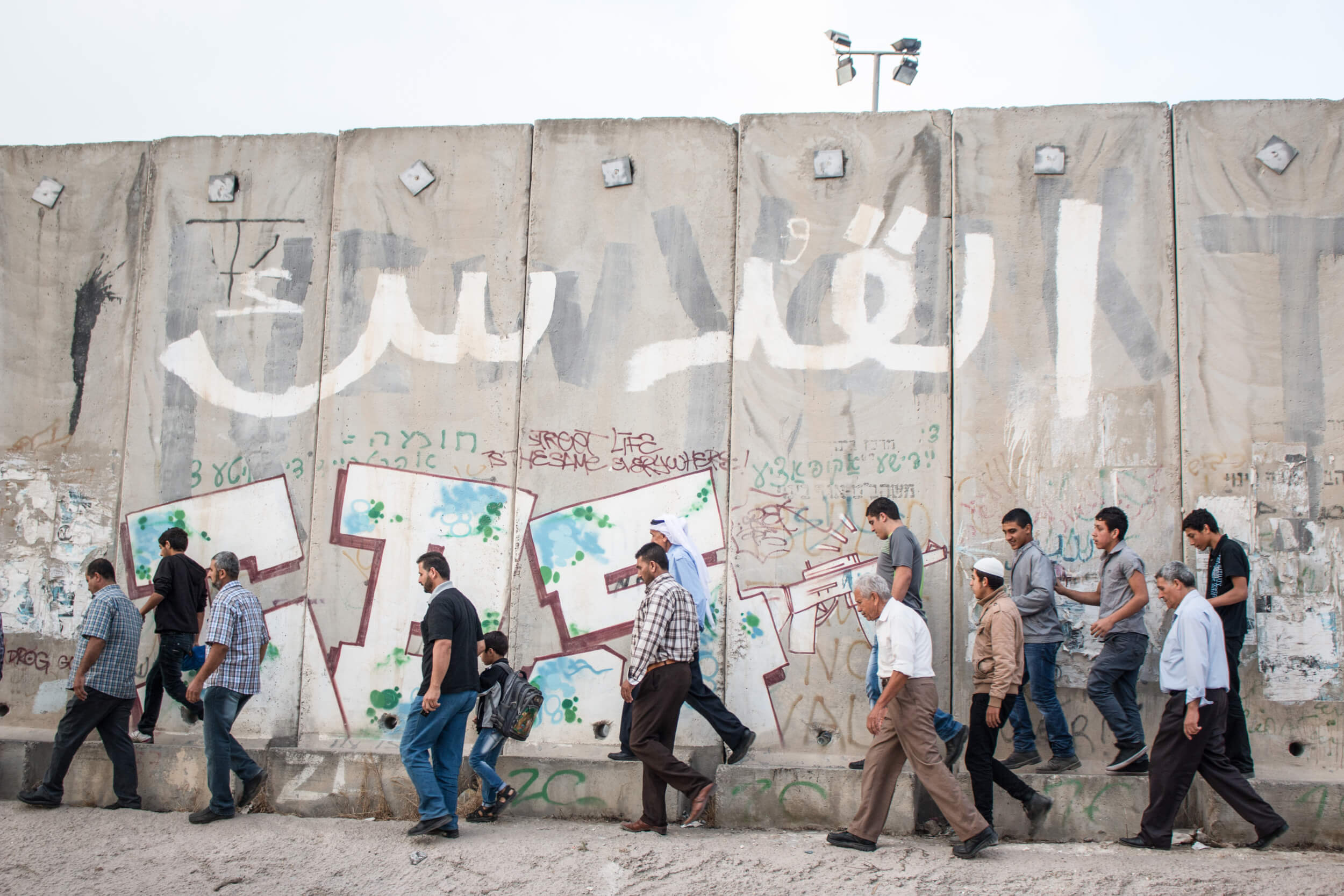 Men walk along the separation wall after dropping off women family members on the adjacent side. (Photo: Karam Saleem)