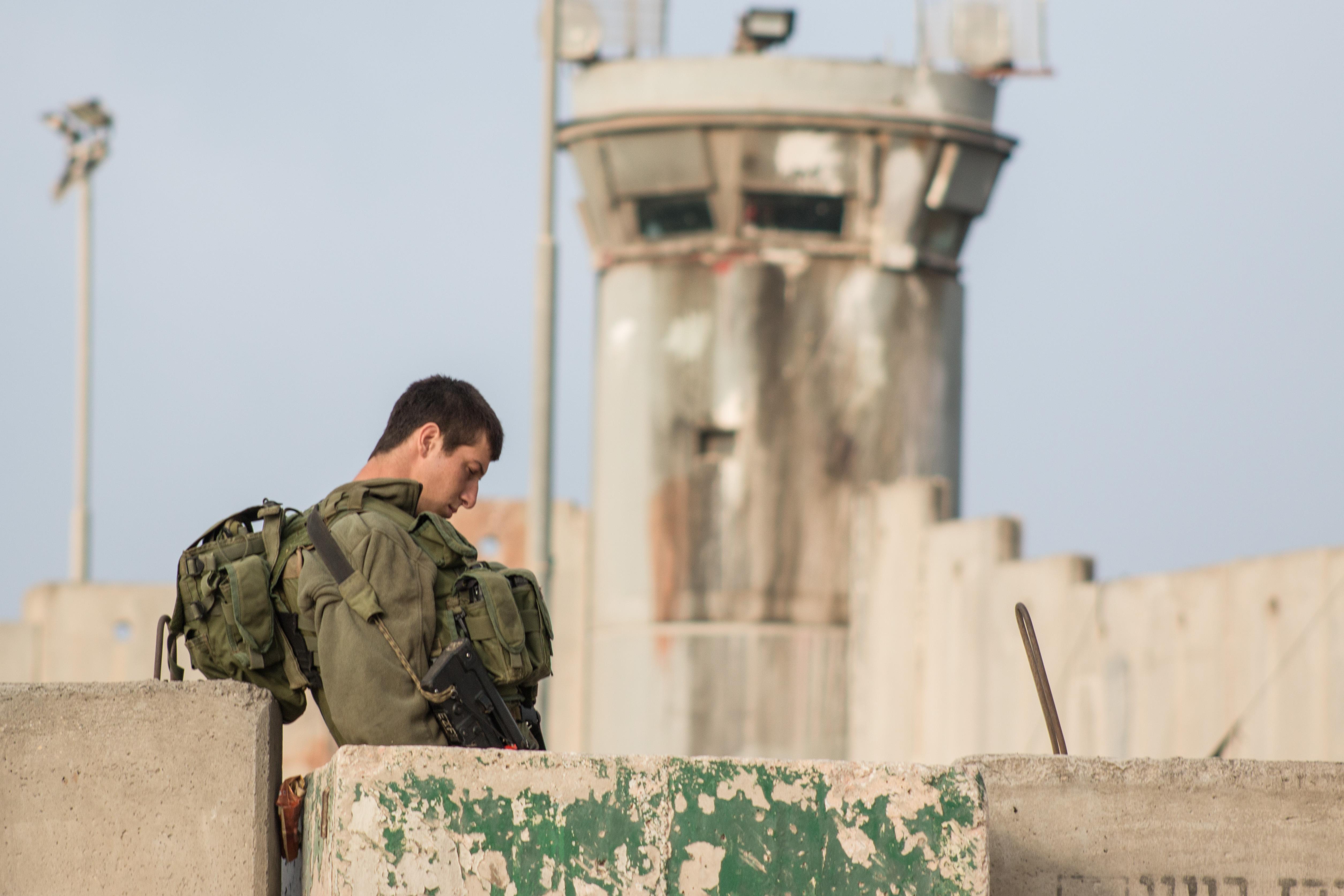 An Israeli soldier stands outside Qalandia checkpoint around 6am. (Photo: Karam Saleem)
