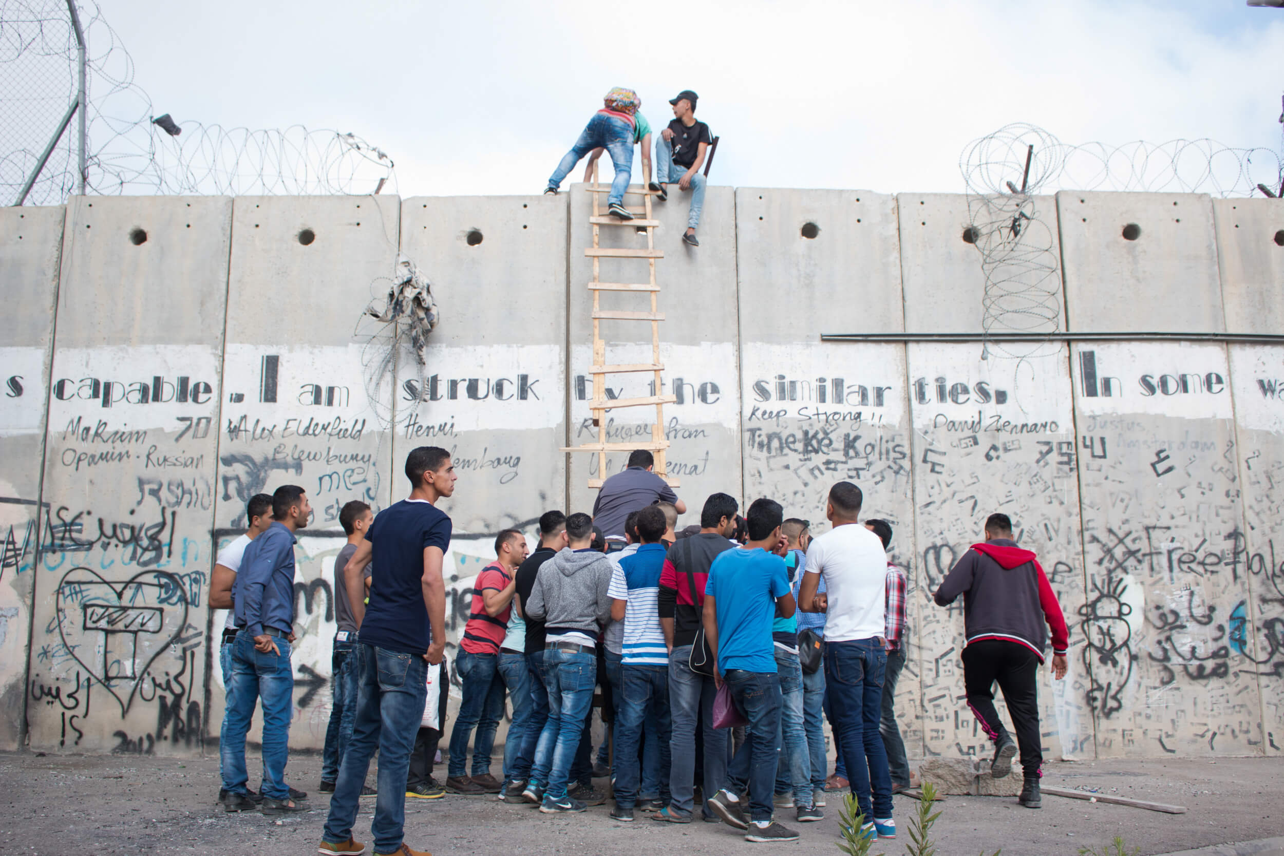 Palestinians gather at a point along the separation wall in Al Ram to illegally cross into Jerusalem with the help of smugglers.  A knotted rope allows them to descend on the other side. (Photo: Karam Saleem)