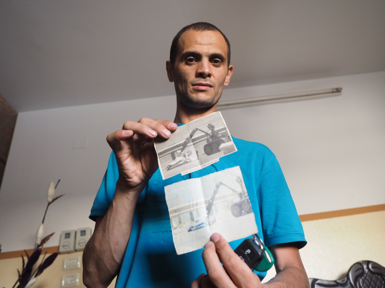 Mohammed Zaidan displays two newspaper clippings of photos of the Israeli bomb disposal robot. (Photo: Dan Cohen)