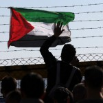 A Palestinian flag is attached to the barbed wires of Israel's Ofer prison in West Bank, while the families wait for the release of Palestinian prisoners (AFP Photo / Abbas Momani)