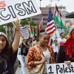 Denver protest, July 2014: Young women march in Palestinian protest, one wears hijab other wearing keffiyeh on head and carries sign about racism, other marchers in background with American flag and Palestinian flags. Photo by Chris Goodwin