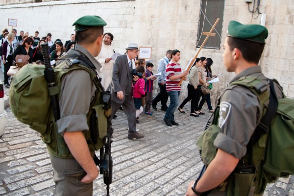 As Israeli soldiers watch, Palestinian Christians lead a procession from the Old City of Jerusalem toward the Garden of Gethsemane in observance of Maundy Thursday, the night Jesus was arrested before his crucifixion, April 5, 2012. (Photo: Ryan Rodrick Beiler)