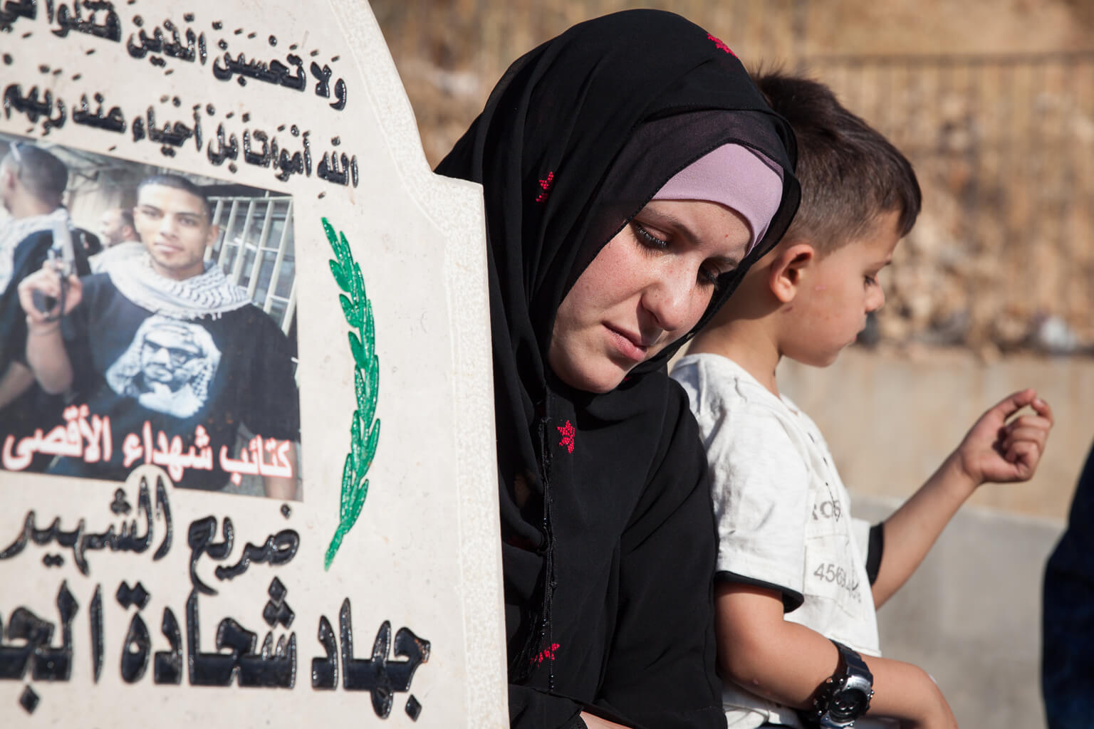 Roula Al-Jafari and her son visit the grave of her husband's cousin, Jihad Al-Jafari.  Jihad, age 20, is the most recent person to be buried at the Martyr's Cemetery. In the early morning hours of February 24, 2015, the Israeli military entered Dheishe Refugee Camp and its residents responded by throwing stones and molotov cocktails.  An Israeli soldier was lightly injured, the army began firing live ammunition at the protestors, and Jihad was shot in the chest. Witnesses reported that the Israeli army prevented rescuers and an ambulance from reaching Jihad, and that he laid on the roof of his home, bleeding, for over an hour. (Photo: Rebecca George)