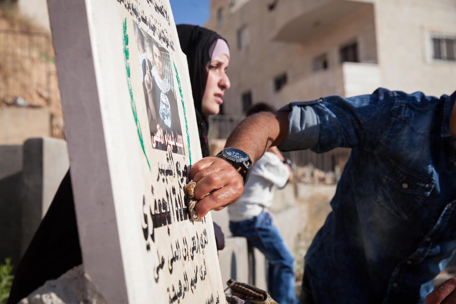 A friend cleans Jihad Al-Jafari's headstone. (Photo: Rebecca George)