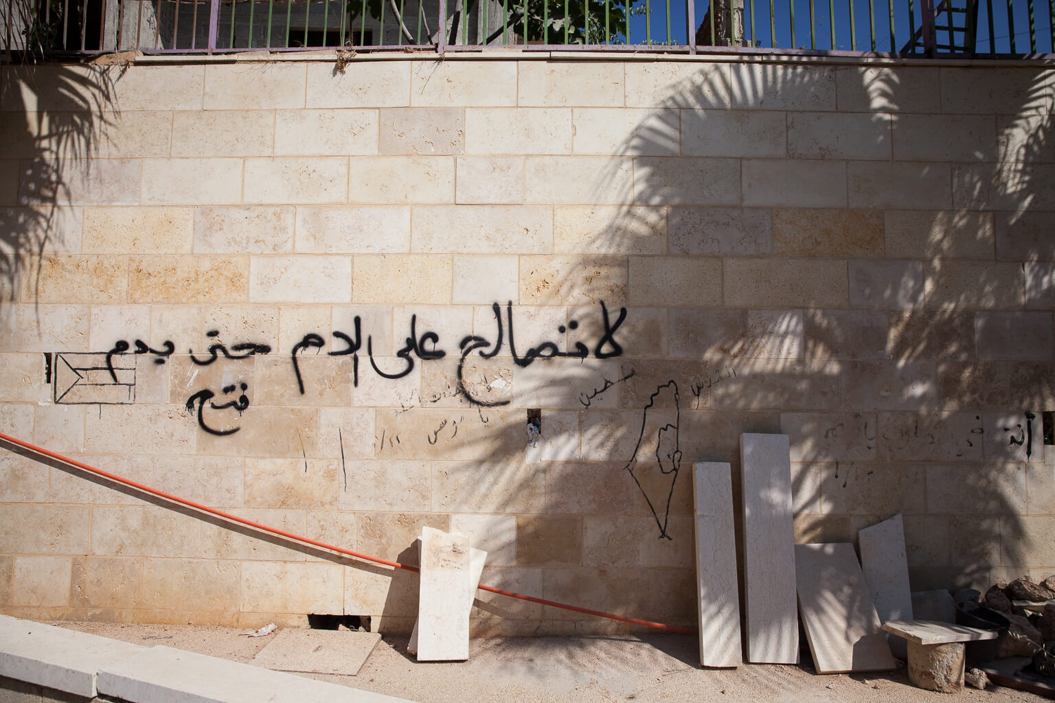 """A Jahili poem decorates the cemetery wall: """"Don't reconcile for blood...even for blood."""" This could be translated colloquially as, """"Don't forgive those who killed your brother, even if you kill his brothers."""" (Photo: Rebecca George)"""