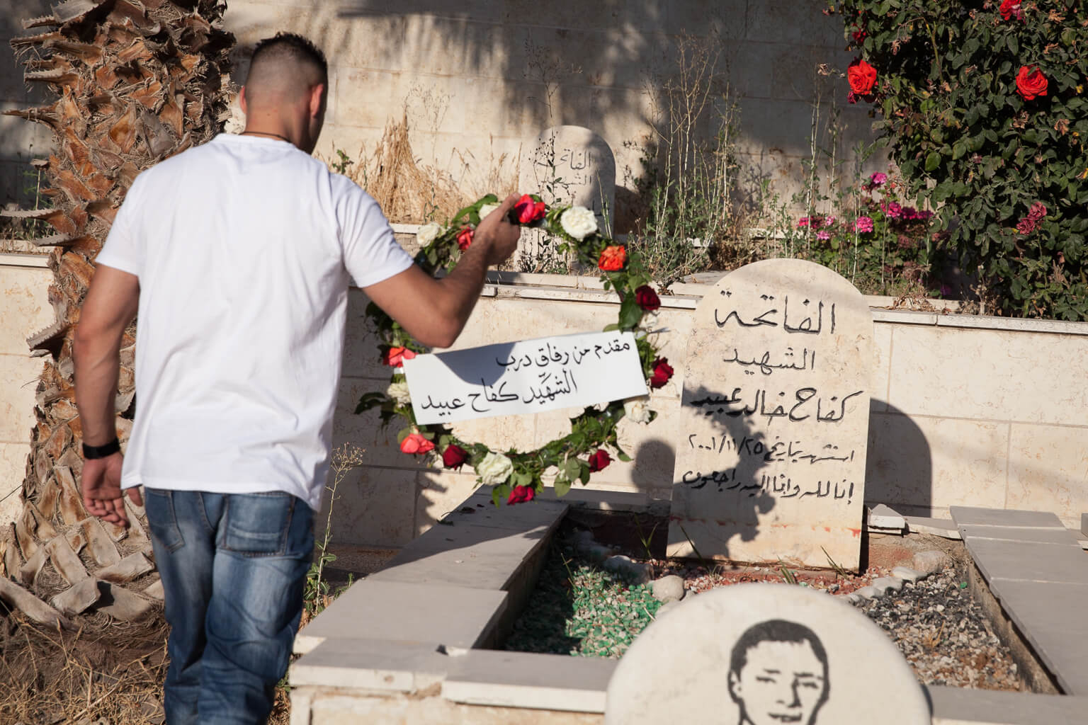 """Milad Obaid hangs a wreath on the grave of his brother, Kifah, who was killed by Israeli forces in 2001 while throwing stones. Kifah was 12 years old. """"Every Eid instead of celebrating like everybody else in the world, we come here,"""" Milad says. """"Nowadays there is no normal world, all the world is broken. Al Eid is a holiday that is supposed to be happy, but we come to the cemetery. We grieve for those we lost, then we go visit our relatives. And this is our life.  It's normal."""" (Photo by Rebecca George)"""