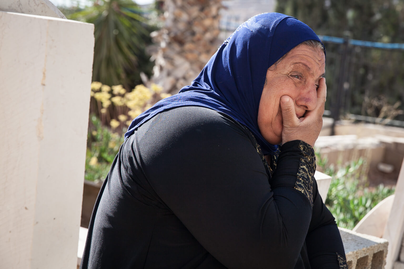 """The mother of Issa Faraj visits her son's grave. Issa's brother, Mohammed, says, """"He was 23 years old. He was shot when he was at home with two bullets by a sniper...When he got shot he was carrying his daughter...Until today the window in his room is witnessing. We kept everything as it is, we didn't change anything."""" He continues, """"It feels like he felt that he was going to join his God, to die, as a martyr."""" (Photo: Rebecca George)"""