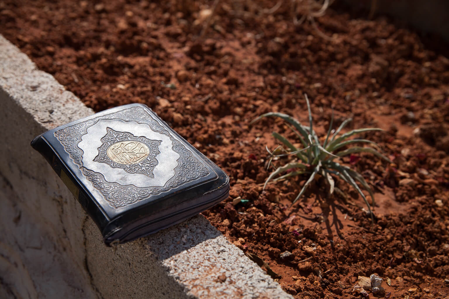 A Koran rests on the grave of Jihad Al-Jafari. (Photo: Rebecca George)