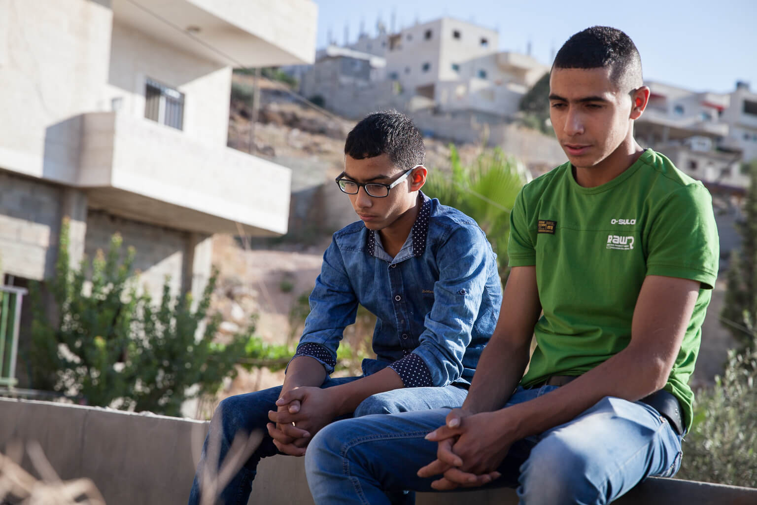 Mahmoud Al-Jafari, brother of JIhad, and a friend, sit at Jihad's grave. (Photo: Rebecca George)