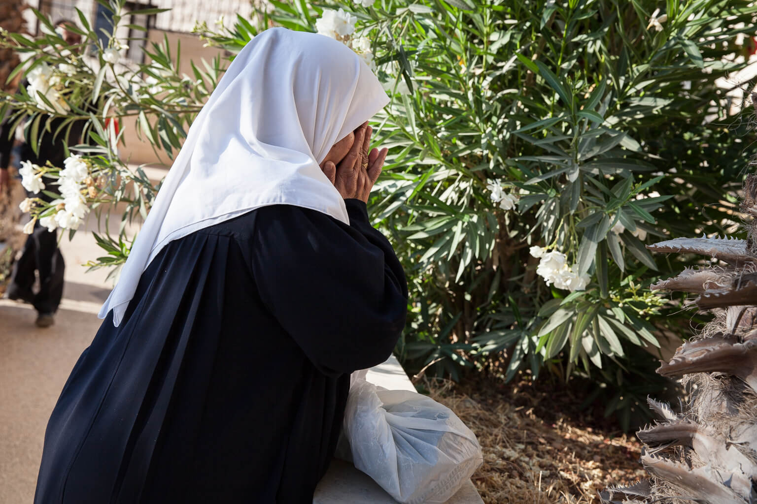 The mother of Abed Al Qader Abu Laban, visits her son who was killed by the during the Second Intifada at the age of 24. He was shot by the Israeli army while throwing stones in Al Khader village. (Photo: Rebecca George)