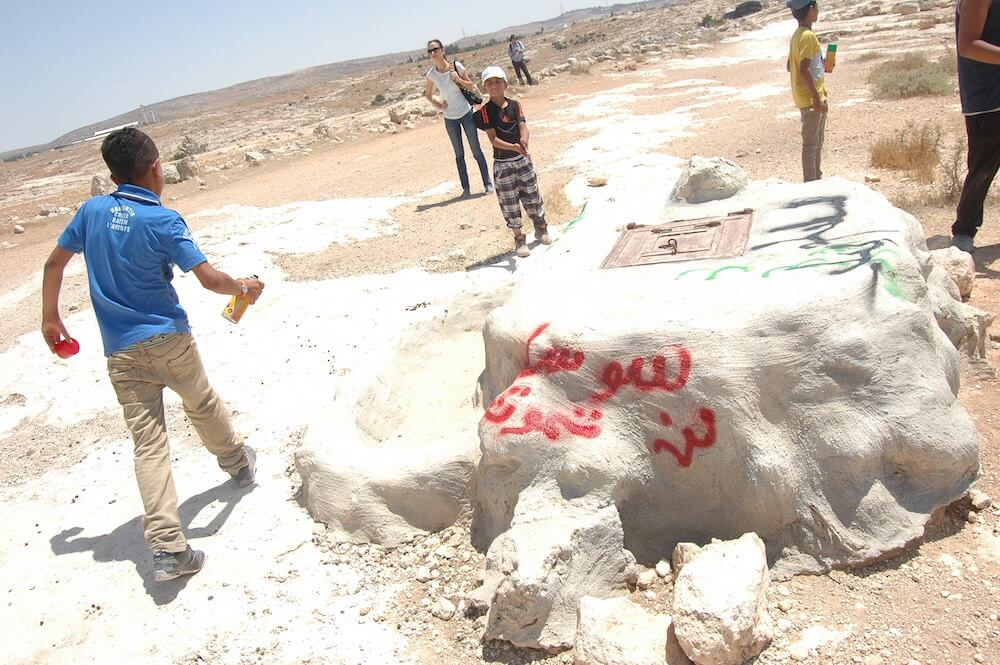 "Young Palestinian protester spray-paints ""Susiya"" on a rock outside of the village, during a protest against the town's scheduled demolition. (Photo: Allison Deger)"