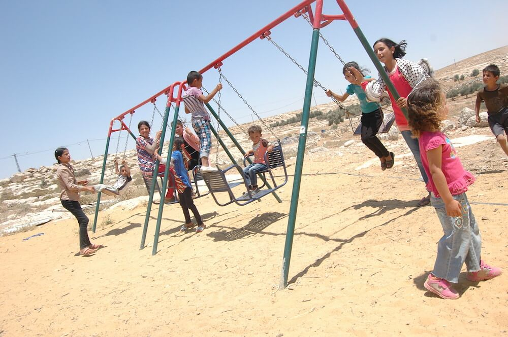 Palestinian children from Yatta in the south Hebron hills play on swings while visiting relatives who live in the village of Susiya, slated for demolition. (Photo: Allison Deger)