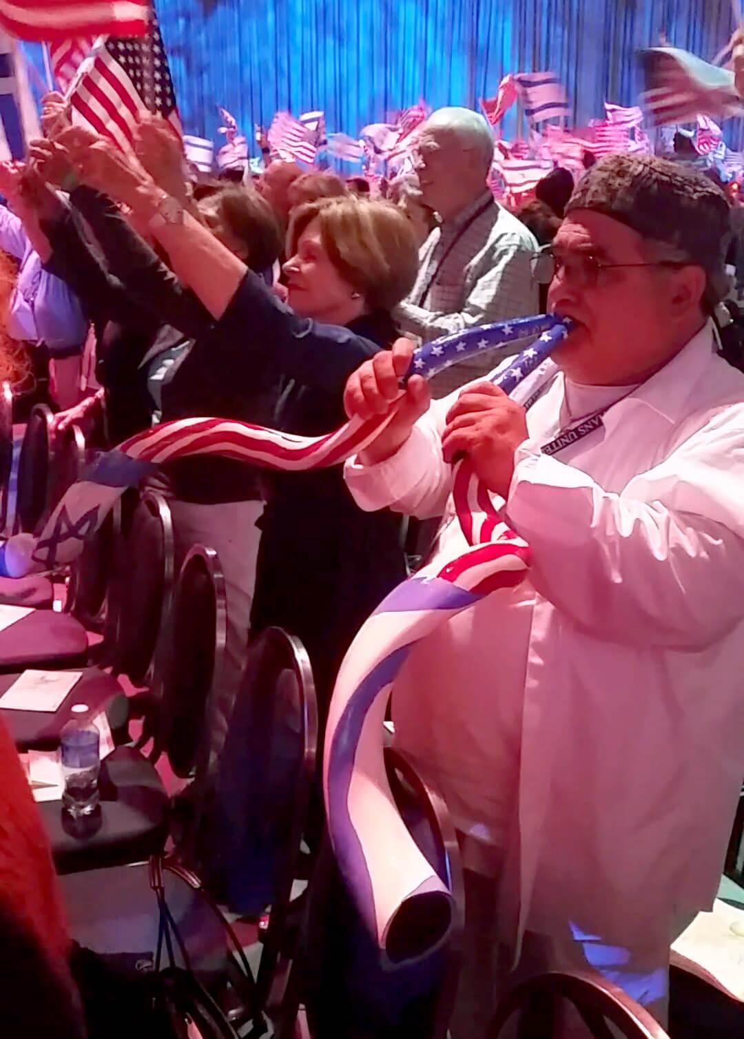 A CUFI attendee with a US/Israeli flag shofar