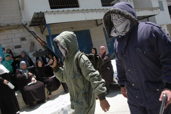 Masked gunmen with l-Aqsa Martyrs' Brigades walk through Qalandia refugee camp, hours after Israeli forces kill 17-year old Mohammed Hani al-Kasbah, Qalandia Refugee Camp. (Photo: Allison Deger)