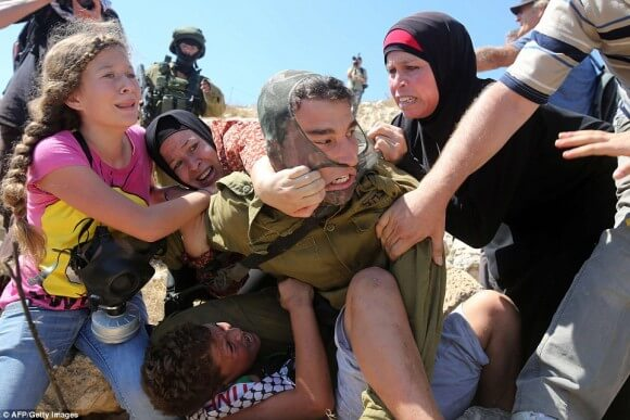 Women and children of Nabi Saleh ambush and unmask armed Israeli soldier attempting to capture a child (photo: AFP/Getty)