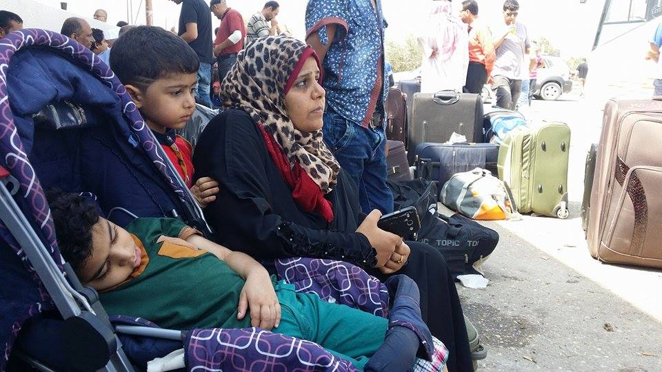 Nada Mumer wants to travel to Egypt to meet her husband. The sleeping boy is her ill son. (Photo: Isra Saleh El-Namy)
