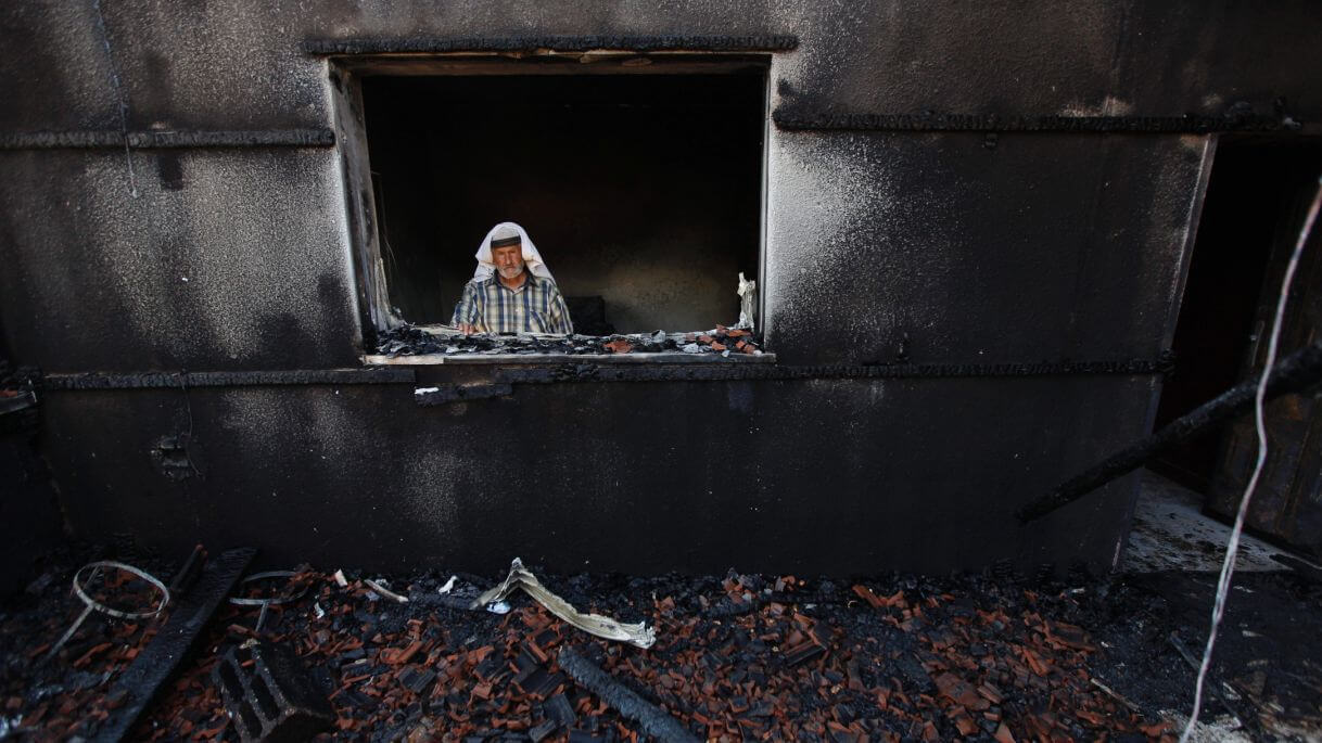 A Palestinian man inspects a house after it was torched, in Duma, near the West Bank city of Nablus, July 31, 2015. (Photo: AP)