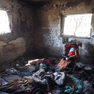 An effigy of baby Ali Dawabshe sits in a melted stroller inside the room where Israeli settlers burned him alive. (Photo: Dan Cohen)