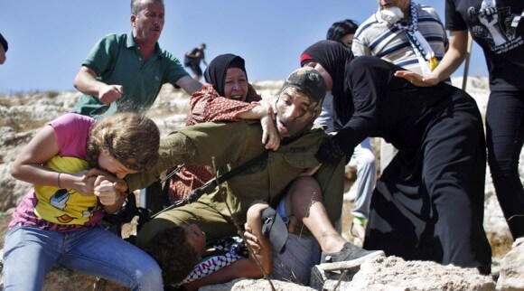 Palestinians rush an Israeli soldier detaining a boy during a demonstration in the West Bank village of Nabi Saleh, near Ramallah, August 28, 2015. (Photo: Mohamad Torokman/Reuters)