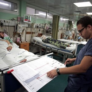 Palestinian physician Allam Nayef checks the report of a patient in the ICU at the Shifa hospital in Gaza City, July 19, 2014, where the power goes off repeatedly under daily rolling blackouts and many items are in short supply. (AP Photo/Khalil Hamra)