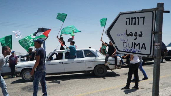 Palestinian men gather at the entrance to the village of Duma before the body of Sa'ad Dawabshe arrives. (Photo: Dan Cohen)