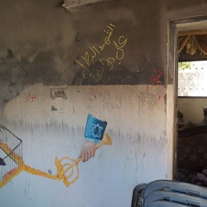 Artwork inside the burned-out Dawabshe home blames the Israeli government for the firebombing. (Photo: Dan Cohen)