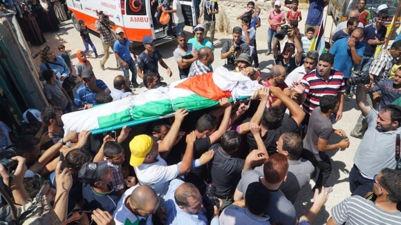 Mourners carry the body of Sa'ad Dawabshe wrapped in a flag. (Photo: Dan Cohen)
