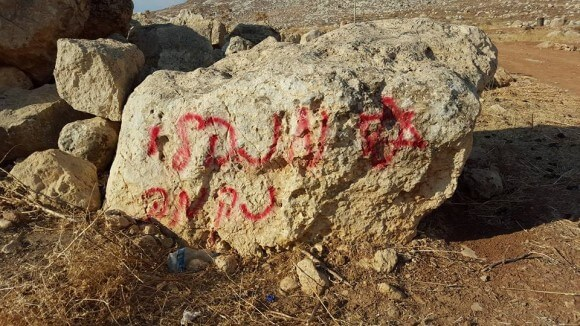 """Arsonists spray paint """"administrative revenge"""" next to burned Bedouin tent. (Photo: Zakaria Sadah/Rabbis for Human Rights)"""