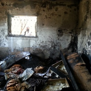 A man from Duma peeks into the bedroom in which toddler Ali Dawabsheh was burned to death. (Photo: Jen Marlowe)