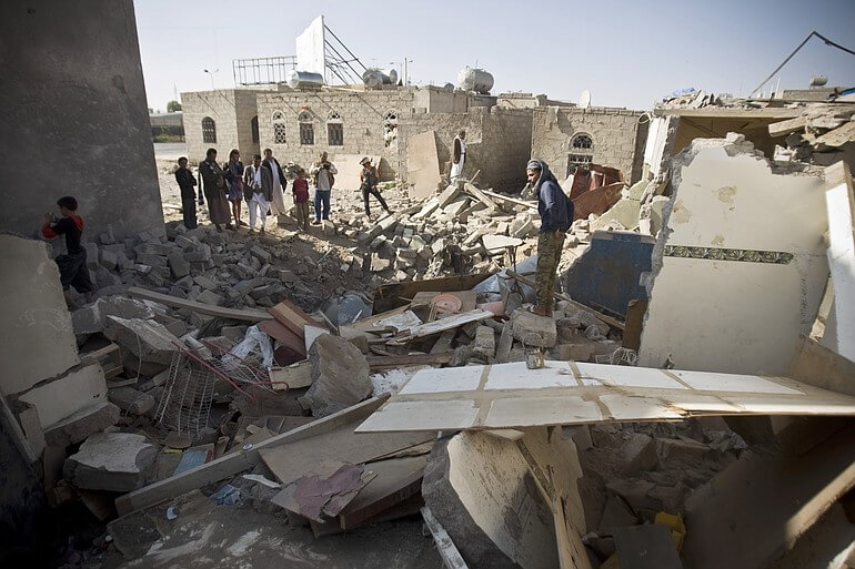 Yemenis in the rubble of homes destroyed by coalition airstrikes in the capital city of Sana'a CREDIT: Hani Mohammed / AP