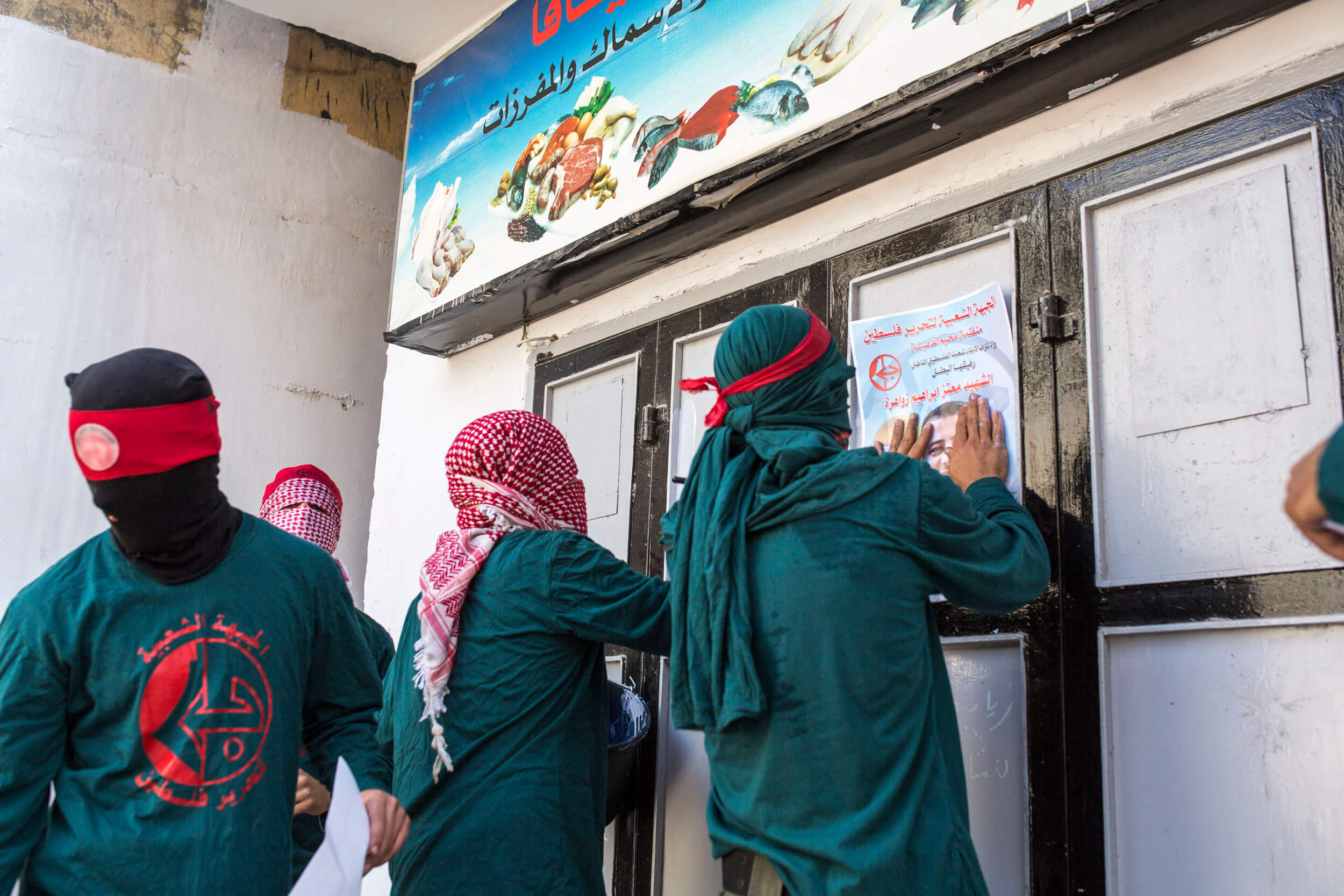 Members of the Popular Front for the Liberation of Palestine glue posters honoring Mutaz Ibrahim Zawahreh, 27, who was killed the day before by the Israeli army. PFLP is very popular in Deheishe refugee camp. (Photo: Anne Paq)
