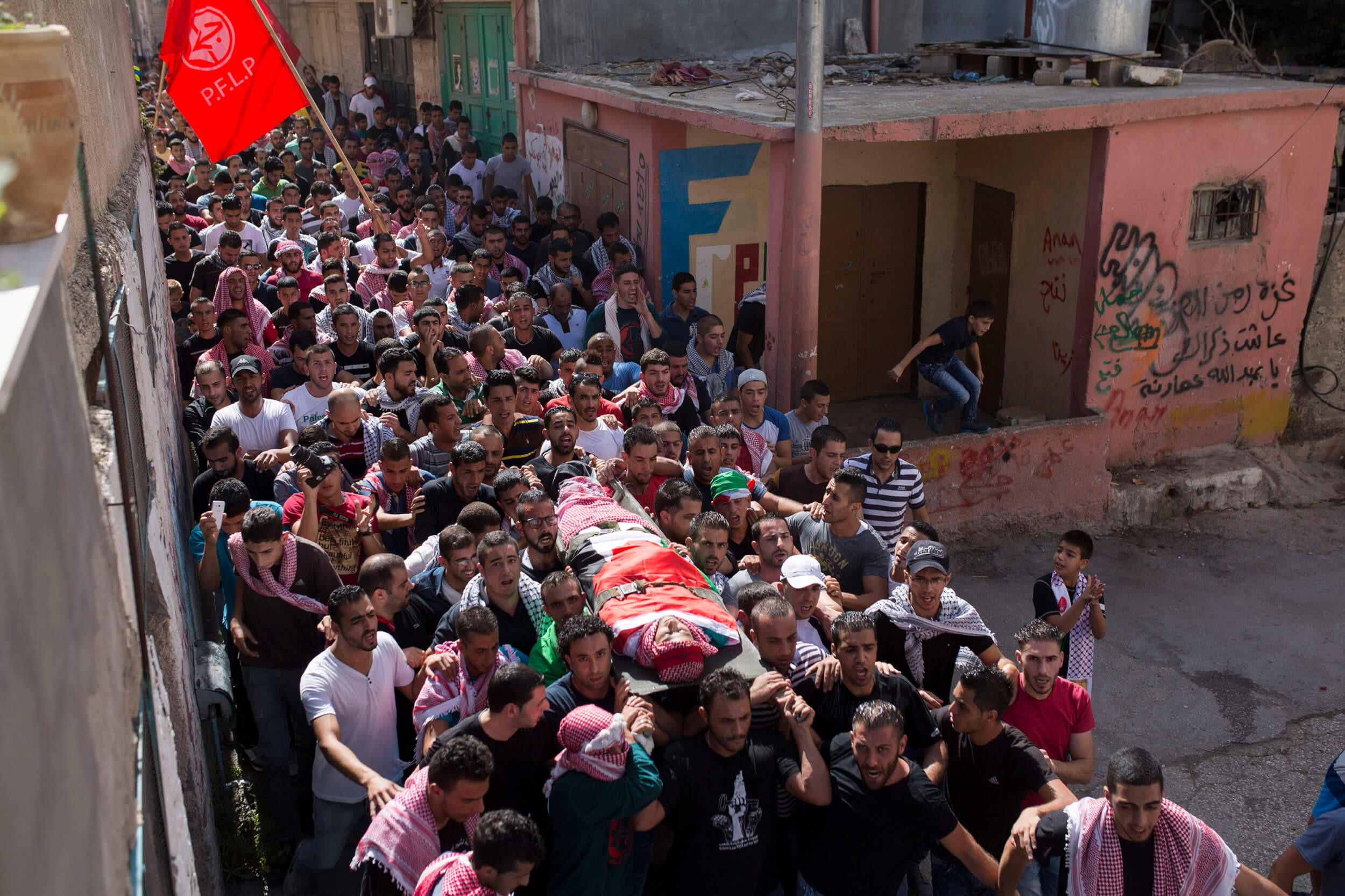 An angry crowd carries the body of Mutaz through the narrow streets of Deheishe. The camp was established in 1949, and is overcrowded, with 13,000 Palestinian refugees. (Photo: Anne Paq)
